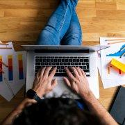 homem sentado no chão, mexendo no computador com gráficos impressos ao lado. Imagem ilustrativa texto franquia de seguradora