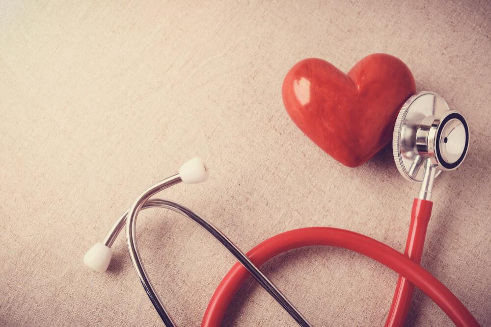 Vemos um estetoscópio apoiado em um coração de plástico vermelho (imagem ilustrativa). Texto: franquias que mais crescem.