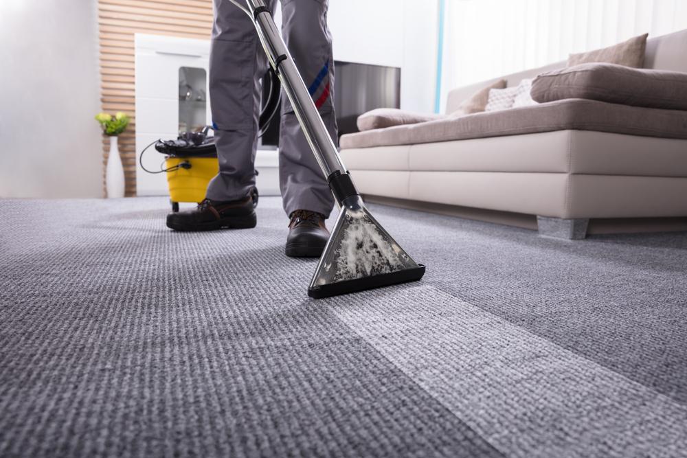 Vemos uma pessoa limpando um carpete com um aspirador de pó e água, aqueles usados por grandes empresas (imagem ilustrativa). Texto: franquias de limpeza.