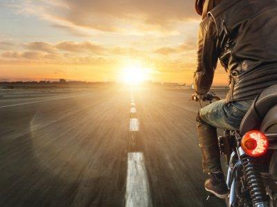 Homem sobre moto em uma estrada com o sol se pondo no horizonte. Imagem ilustrativa texto franquia moto peças