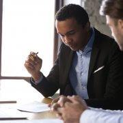 Dois homens conversando e analisando um documento. Imagem ilustrativa texto franquia para corretor de seguro
