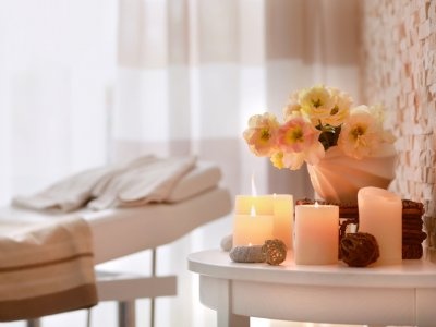 Maca para fazer massagem ao fundo com velas acessas em uma mesa de canto com girassóis. Imagem ilustrativa texto franquias compactas