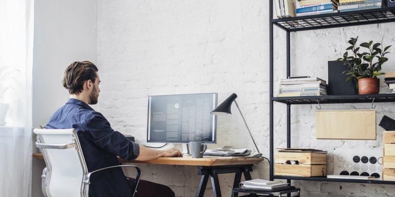 Homem em frente ao computador trabalhando em sua casa. Imagem ilustrativa texto franquias home based