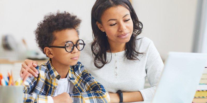 Criança ao lado de uma mulher estudando por meio do notebook. Imagem ilustrativa texto franquias público infantil