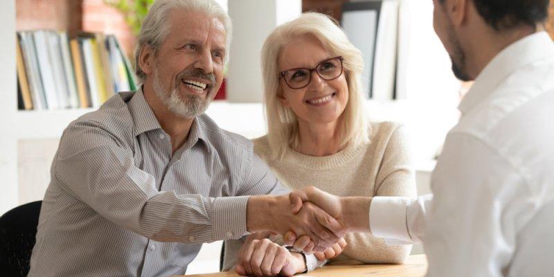 Casal com cabelos grisalhos apertando a mão de um empresário após assinar um documento. Imagem ilustrativa texto franquias que dão certo.