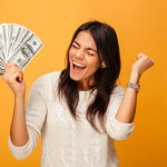 Mulher segurando dinheiro e comemorando. Fundo amarelado. Imagem ilustrativa texto franquias que mais crescem