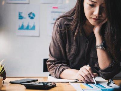 Mulher analisando dados com caneta e uma calculadora ao lado. Imagem ilustrativa texto franquias virtuais