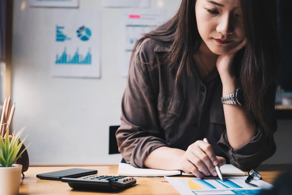 Vemos uma mulher analisando dados com caneta e uma calculadora ao lado   (imagem ilustrativa). Texto: melhores franquias para investir.