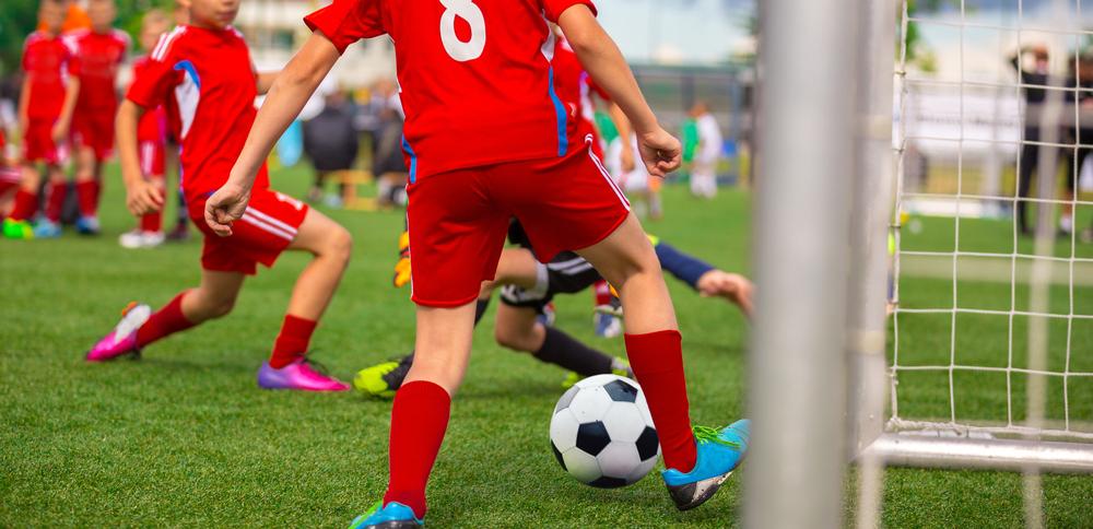 Vemos algumas crianças (não é possível ver os seus rostos) jogando futebol em um campo gramado. Eles estão trajando um uniforme vermelho (imagem ilustrativa). Texto: franquia público infantil.