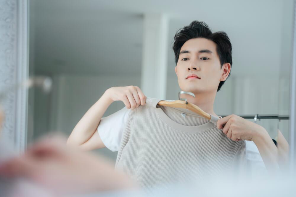 Vemos um homem de frente para um espelho. Ele segura uma camiseta em um cabide. Seu semblante sério indica determinação com a escolha da peça (imagem ilustrativa). Texto: franquia de moda masculina.