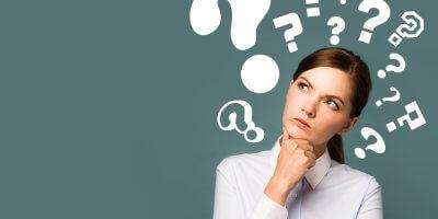 Mulher com vários pontos de interrogação ao lado de sua cabeça. Imagem ilustrativa texto investir em franquias