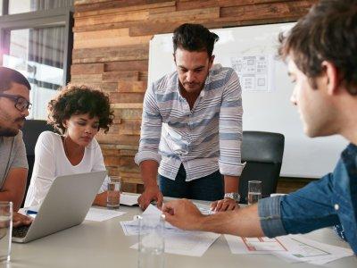 Pessoas conversando em uma sala de reunião sobre algum planejamento. Imagem ilustrativa texto melhores franquias para investir