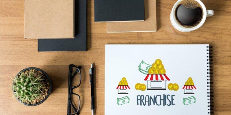 Mesa organizada com xicara de café, oculos, caderno, caneta, tablet e um pequenos cactus. Caderno com desenho de uma loja e escrito franchising. Imagem ilustrativa texto microfranquias on-line
