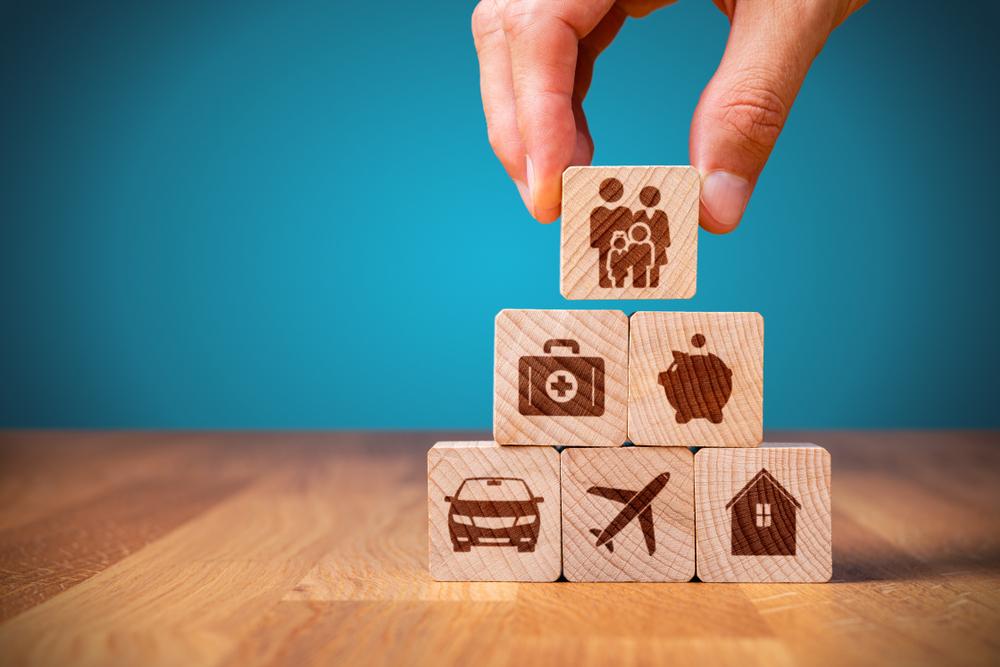 Vemos seis blocos de madeira sendo empilhados. Em cada um está grafado um símbolo relacionado ao ramo de seguros. Temos uma família; uma maleta de remédios, indicando saúde; um cofre de porquinho, indicando finanças; um carro; um avião, indicando uma viagem e uma casa (imagem ilustrativa). Texto: franquia de seguradora.
