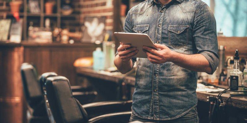 Homem segurando tablet enquanto espera um cliente em sua barbearia. Imagem ilustrativa texto montar um negócio lucrativo