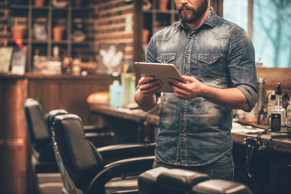 Homem segurando tablet enquanto espera um cliente em sua barbearia. Imagem ilustrativa texto melhores franquias para investir