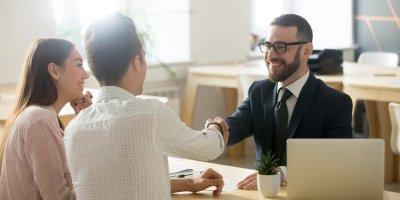 Casa apertando as mãos de um cara com gravata após assinar um contato. Imagem ilustrativa texto pequenas franquias de sucesso.