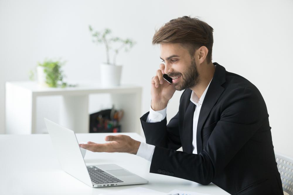 Homem conversando ao telefone e olhando para a tela de seu notebook em uma sala totalmente branca.