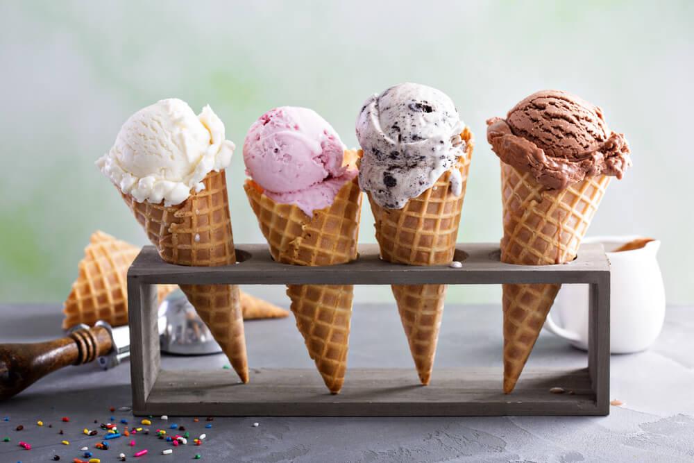 Vemos quatro sorvetes em casquinhas com sabores diferentes: temos creme, morango, flocos e chocolate.