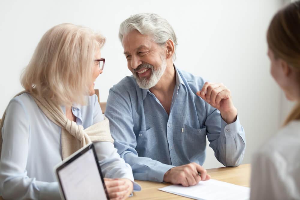Casal de idosos fechando contrato com uma pessoa à sua frente, sentados a mesa e sorrindo um para os outros. Imagem ilustrativa da contratação de um plano de saúde