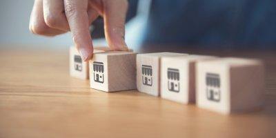blocos de madeira com símbolo de loja e uma sendo destacada. Imagem ilustrativa texto vantagens da microfranquia