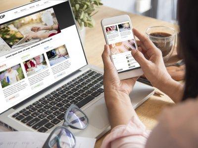 Mulher mexendo em sua loja virtual pelo celular e analisando também pelo computador. Imagem ilustrativa texto como abrir uma franquia.