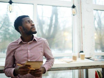 Homem dentro de seu escritório olhando para o alto e com uma prancheta. Imagem ilustrativa texto franqueador