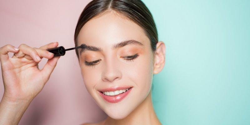 mulher passando maquiagem com fundo bicolor rosa e verde claro. Imagem ilustrativa texto franquia bellaza.