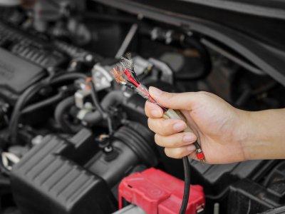 Homem segurando fios cortados de um motor. Imagem ilustrativa texto franquia de automóveis