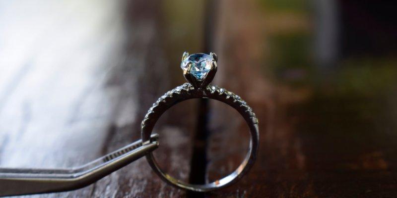 Anel apresentado sobre uma mesa de madeira com uma pedra de diamante no topo dele. Imagem ilustrativa texto franquia mazze