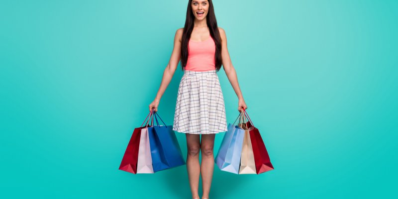 Mulher com compras em sacolas de shoppings com fundo esverdeado. Imagem ilustrativa texto franquia para shopping