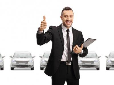 Homem com prancheta e terno dando sinal de joia na frente de uma fileira de carros. Imagem ilustrativa Franquia Reduza Veículos.