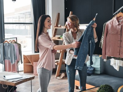 Mulher oferecendo uma roupa para cliente mulher em sua loja. Imagem ilustrativa texto franquias baratas de roupas
