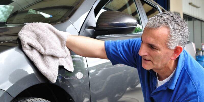Homem com cabelo grisalho limpando um carro. Imagem ilustrativa texto franquias baratas para aposentados.