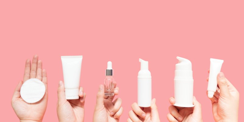 Várias embalagens de cosméticos sendo seguradas por mãos femininas num fundo rosa. Imagem ilustrativa texto franquias de cosmeticos