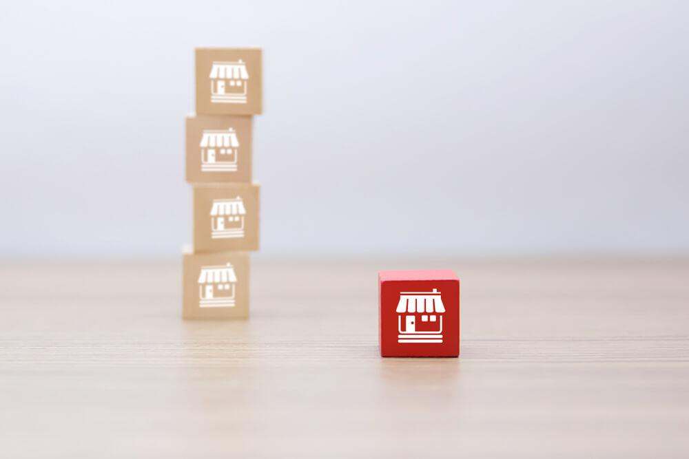 blocos com imagem de lojas na face formando um fila. Bloco em destaque vermelho. Imagem ilustrativa texto franquias baratas para aposentados.