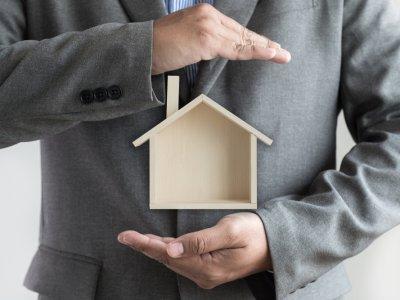 Homem segurando uma casa em maquete sobre seus braços. Imagem ilustrativa texto franquias mais baratas do Brasil