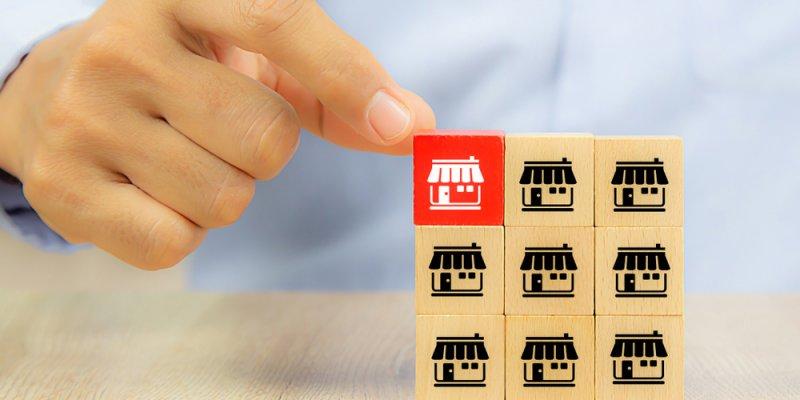 bloquinhos de madeira com simbolos de lojinhas. Bloco superior esquerdo em vermelho. Imagem ilustrativa texto investir em franquias
