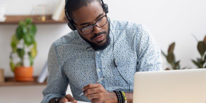 Homem estudando em frente ao computador e fazendo anotações. Imagem ilustrativa texto melhores franquias baratas