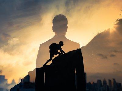 Homem escalando uma montanha. Sombra de um homem olhando para o horizonte. Imagem ilustrativa texto vantagens de ser um franqueador.
