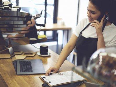 mulher com notebook na mesa, pracheta ao lado e conversando no celular dentro de seu estabelecimento. Imagem ilustrativa texto como montar uma franquia