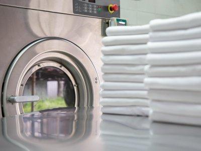 Espaço de uma lavanderia com máquina de lavar ao fundo e algumas toalhas dobradas a frente. Imagem ilustrativa texto franquia #1 lavanderia.