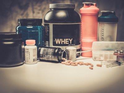 Vários suplementos alimentares para praticantes de exercícios físicos sobre uma mesa. Imagem ilustrativa texto franquia brasil nutri shop.