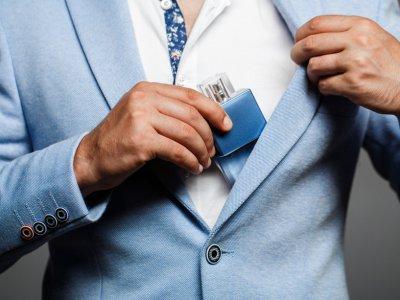 Homem com terno azul guardando um perfume azul dentro do paletó. Imagem ilustrativa texto franquia casa prado.