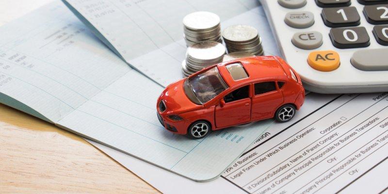 Carrinho de brinquedo sobre algumas contas, com moedas ao lado e calculadora. Imagem ilustrativa texto Franquia Chipbras