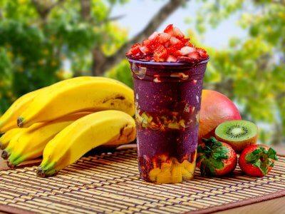 Copo com o creme de açaí misturado com algumas frutas. Ao lado, uma penca de manga, uma manga, kiwi e morando. Imagem ilustrativa texto franquia cream berry