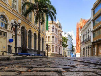 Uma das ruas calçadas de recife com prédios coloniais e céu azul. Imagem ilustrativa texto franquia encontre sua viagem