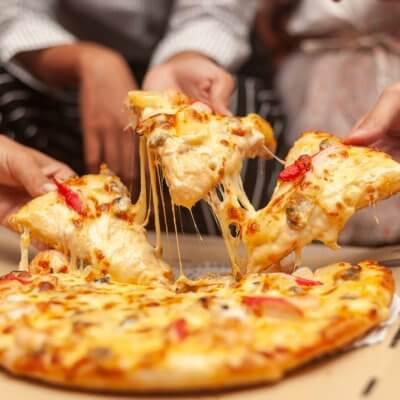 Grupo de pessoas comendo uma pizza em casa. Imagem ilustrativa texto franquia fórmula pizzaria.