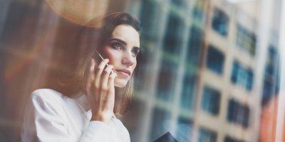 Mulher conversando ao telefone em um prédio comercial. Imagem ilustrativa texto franquia primeiro mundo
