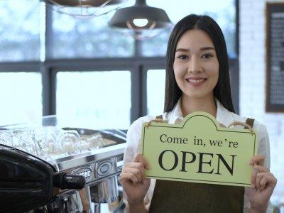 mulher segurando placa de aberto em uma cafeteria. Imagem ilustrativa texto negócio fgts